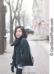 Young Asian woman walking on street.