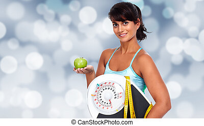 Young asian woman with apple and scales.