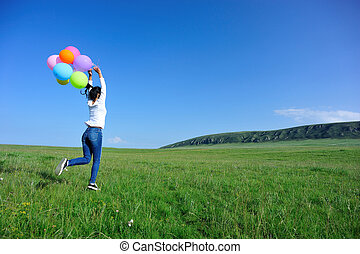young asian woman with balloons on green grassland