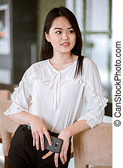 Asian woman with black long straight black hair wearing white blouse
