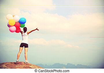 young asian woman with colored balloons on mountain pea