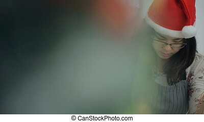 Young Asian woman with glasses and cap of Santa prepare decorations.
