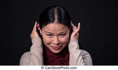 Young asian woman with long hair on dark background. - Young...
