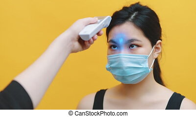 Young asian woman with medical mask getting her body temperature checked with laser thermometer. Coronavirus prevention. High quality 4k footage