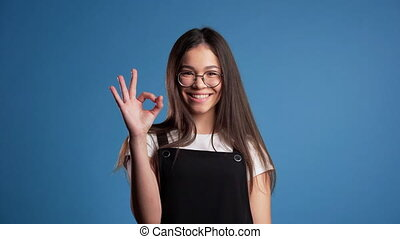 Young asian woman with perfect make-up making OK sign over blue background. Winner. Success. Positive girl smiles to camera. Body language.