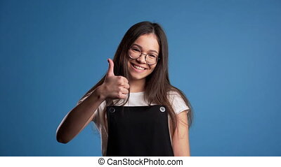 Young asian woman with perfect make-up making thumbs up sign over blue background. Winner. Success. Positive girl smiles to camera. Body language.