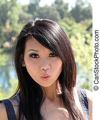 Young Asian woman with surpised expression outdoors