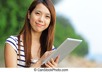 young asian woman with tablet outdoor