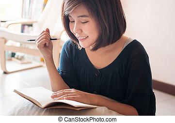Young asian woman writing.