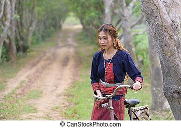 Young asian women haul bike on standing in area field