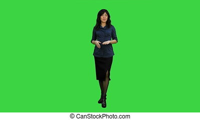 Young asian women standing and talking to a camera on a Green Screen, Chroma Key