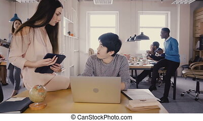 Young Asian worker talking to female team leader. Happy...