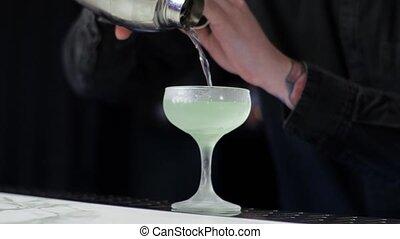 Young aspiring bartender trainee preparing a daiquiri cocktail. Careless guy.
