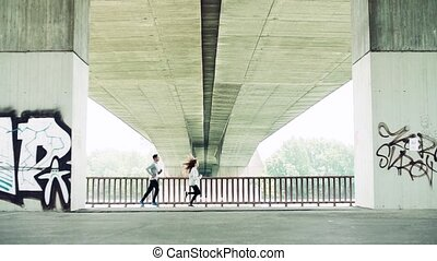 Young athlete couple running under the bridge in the city. -...