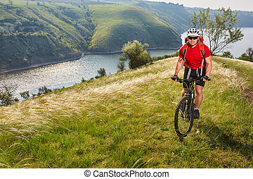Young athlete cylcist riding mountain cycle on the hill above the river in the countryside.