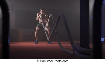 Young athlete doing exercise with rope.