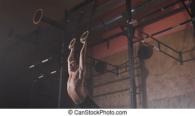 Young athlete doing exercises on the rings.