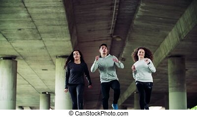 Young athlete friends running under the bridge in the city....