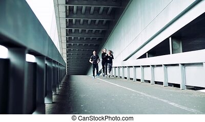 Young athlete friends running under the bridge in the city.