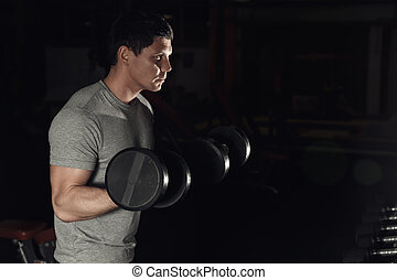 Young Athlete In The Gym Performing Biceps Curls With A Dumbbells.