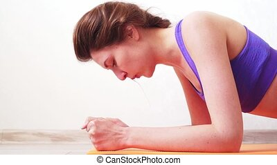 Young athlete makes efforts and perseverance when doing the plank. It is difficult for a woman to keep weight on her elbows and arms slowmo