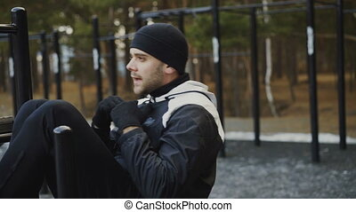 Young athlete man doing exercise on abdominals muscles at outdoor gym in winter park