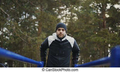 Young athlete man doing push-ups exercise on bars in winter park outdoors