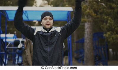 Young athlete man doing warm-up before workout training in winter park