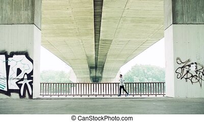 Young athlete man running under the bridge in the city. -...