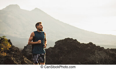 Young athlete man trail running in mountains