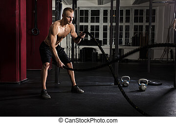 Man Using Training Ropes In A Gym