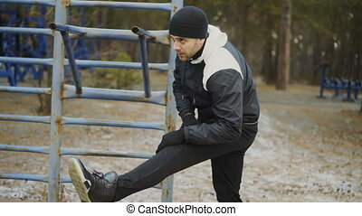 Young athlete man warming up before workout training in winter park