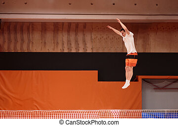 Young athlete on the trampoline in graceful flight.