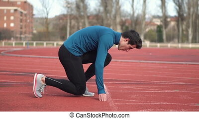 Young athlete preparing at start line and making starting from block. Single track and field sprinter in a stadium starting out of the block, Close-up, slow motion .