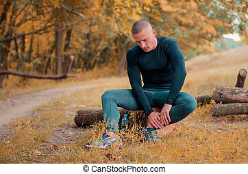 young athlete runner sits on a log holding an ankle with his hands after cramping