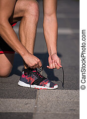 Young athlete, runner tie shoelaces in shoes