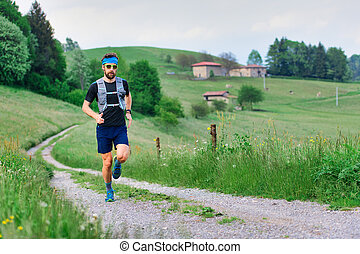 Young athlete with beard runs in rural hill landscape