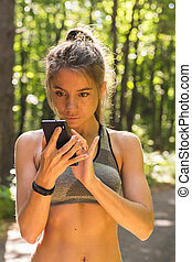 Young athlete woman checking fitness progress on her smart watch. Female runner using fitness app to monitor workout performance.