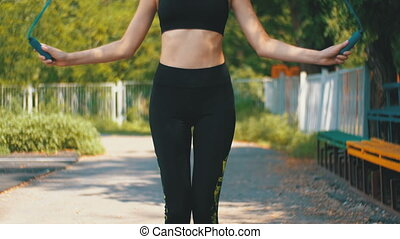 Young Athlete Woman in Comfortable Sport Outfit Jumping Rope...