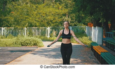 Young Athlete Woman in Comfortable Sport Outfit Jumping Rope on a Sports Field in the Park