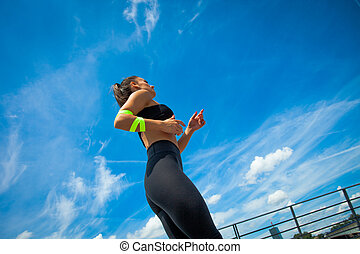 young athlete woman jogging in the city sunny summer day