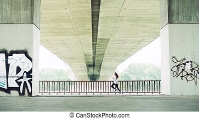 Young athlete woman running under the bridge in the city.