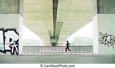 Young athlete woman running under the bridge in the city. -...