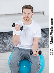 young athlete working out with dumbbells
