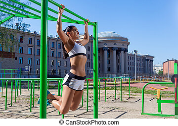 woman doing pull-up - Young athletic brunette woman doing...