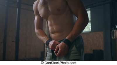 Young athletic Caucasian man changing, putting weight lifting straps on in gym locker room before workout slow motion. ties arms to barbell with fitness straps. . High quality 4k footage