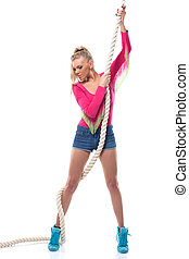 Young athletic girl posing with rope