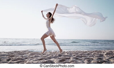 Young athletic girl running on ocean beach with huge silk ...
