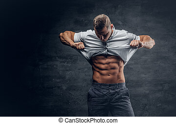 Young athletic male shows six pack ABS. - Young athletic...