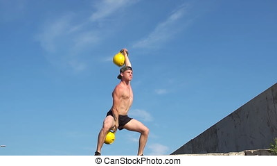 Young athletic man doing exercise gorilla weights outdoor....